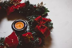 Christmas wreath, candle and greeting card on a white textured background royalty free stock image