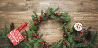 Christmas wreath, coffee, gifts, cup of cocoa on wooden board. Flat lay. Top view. royalty free stock photos