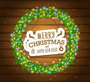 Christmas wreath, colourful glowing garland, lights. Wood texture. Greeting cards Royalty Free Stock Image