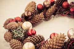 Christmas wreath from cones and balls on wooden board. Toned image Royalty Free Stock Images