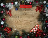 Christmas wreath with a congratulatory inscription on a wooden b. Ackground .photo with place for text Royalty Free Stock Image