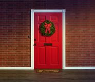 Christmas wreath on red front door with welcome mat. Christmas wreath decorates bright red entry door with welcome mat, brick wall and wood porch floor royalty free stock photos
