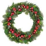 Christmas Wreath Decoration. With red baubles, holly, mistletoe, snow covered juniper fir, blue spruce, cedar and ivy leaves on white background Stock Photography