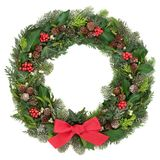 Christmas Wreath Decoration. With a red bow, holly, mistletoe, snow covered juniper fir, blue spruce, cedar, pine cones  and ivy leaves on white background Royalty Free Stock Photo