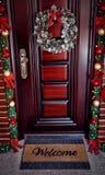 Christmas wreath with decorations on door - welcome doormat. Christmas wreath with decorations on door - welcome door mat stock photo