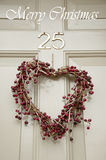 Christmas wreath on a door. Wreath in shape of heart is hanging at the door as a Christmas decoration Royalty Free Stock Photography