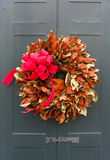 Christmas wreath on a door. Colorful holiday wreath made out of leafs on a wooden black old style door with a red bow royalty free stock photography