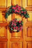 Christmas wreath on door. Colourful Christmas wreath made from artificial branches, cones and flowers, hanging on a front door stock photography