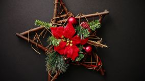 Christmas wreath with dry twigs, pine branches, red balls. And poinsettia flower on wooden star shaped decoration isolated on black background. Flat lay. Top stock footage
