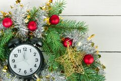 Christmas wreath of fir branches, clocks and bright balls. Flat lay, top view. Christmas or New Year ornament. Christmas wreath of fir branches, clocks and royalty free stock photo