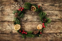 Christmas wreath of Fir branches, cones, red decoration on wooden background with snowflakes. Xmas and Happy New Year theme. Flat lay, top view royalty free stock image
