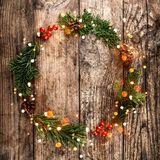Christmas wreath of Fir branches, cones, red decoration on wooden background with snowflakes. royalty free stock photos