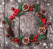 Christmas wreath of Fir branches, cones, red decorations on dark wooden background. royalty free stock image