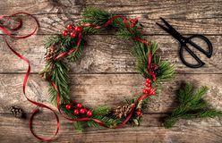 Christmas wreath of Fir branches, cones, scissors and skein of jute on dark wooden background. Xmas and Happy New Year theme, snowflakes. Flat lay, top view royalty free stock image