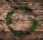Christmas wreath of Fir branches, cones on wooden background stock photography