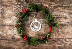 Christmas wreath of Fir branches, pine cones, berries and decoration of wood on rustic background. Xmas and Happy New Year theme royalty free stock photography