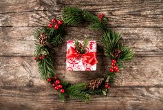 Christmas wreath of Fir branches, pine cones, berries and gift box on wooden background. Xmas and Happy New Year composition royalty free stock image