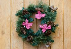 Christmas wreath with fir cones on wooden wall Stock Photo