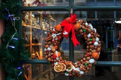 Free Christmas Wreath From Nuts, Tangerines, Cinnamon And Red Bow On Door Stock Photos - 162520863