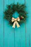 Christmas wreath with gold bow hanging on antique teal blue wooden background Stock Image