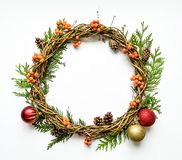 Christmas wreath of vines with decorative ornaments, thuja branches, rowanberries and cones. Flat lay, top view. Christmas wreath of grape vines with decorative stock photos