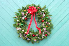 Christmas Wreath on green. Christmas Wreath with ornaments on green wood wall Stock Photo