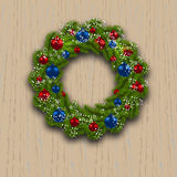 Christmas wreath. Green branch of fir with red, blue balls and snowflakes on a background of wood. Christmas cards. Vector illustration Royalty Free Stock Image