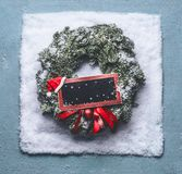 Christmas wreath with green fir branches and red framed sign and Santa hat in snow on blue background, top view with chalkboard. Copy space for your text or stock photos