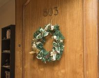 Christmas Wreath Hanging on Brown Wooden Door of Room 803 royalty free stock photography