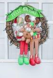 Christmas wreath hanging on the door with the inscription in Spanish - `Happy Christmas` Feliz Navidad stock image