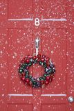 Christmas wreath hanging on door with snowfall royalty free stock photo
