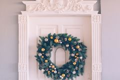 Christmas wreath hangs on the door. Christmas wreath hanging on the white door of the house, close-up royalty free stock photos