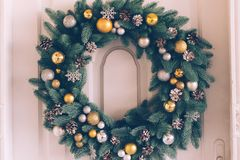Christmas wreath hangs on the door. Christmas wreath hanging on the white door of the house, close-up royalty free stock images