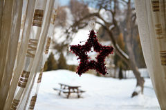 Christmas wreath hanging on window. Christmas star shaped wreath hanging on window with a view to the outside yard covered by snow stock images