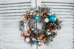 Christmas wreath hanging on wooden blinds. Blue color Stock Photos