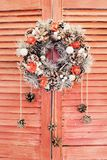 Christmas wreath hanging on wooden blinds. Red shutters or door Royalty Free Stock Photography