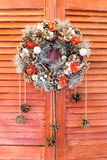 Christmas wreath hanging on wooden blinds. Red shutters or door Royalty Free Stock Images