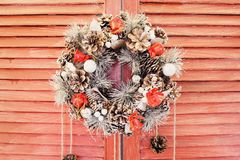 Christmas wreath hanging on wooden blinds. Red shutters or door Stock Images