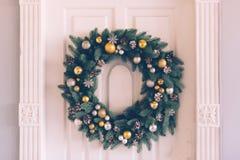 Christmas wreath hangs on the door. Christmas wreath hanging on the white door of the house, close-up Stock Photography