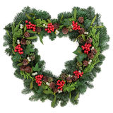 Christmas Wreath. Christmas heart shaped wreath with holly mistletoe, ivy, pine cones and winter greenery over white background royalty free stock photo