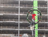 Christmas wreath on light pole in front of building under construction. royalty free stock images