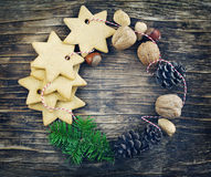 Christmas wreath made from cookies, nuts, pine cones and fir branches. On wooden background stock photos