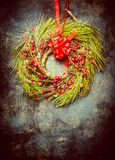 Christmas wreath made of fir branches and red winter berries on vintage background. Royalty Free Stock Photos