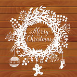 Christmas wreath made of leaf and flower on table top, winter  door decoration, white paper and wood background. Greeting card tem Stock Photo