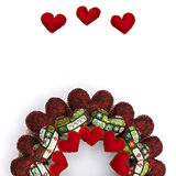 Christmas wreath made with patchwork red hearts half on white background. Half Christmas wreath made with patchwork red and patterned hearts isolated on white stock image