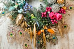 Christmas wreath made of pine branches decorated with peacock feathers, toys and plants royalty free stock images