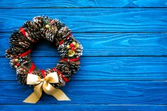 Christmas wreath made of pine cones on blue wooden background top view copy space. Christmas wreath made of pine cones on blue wooden background top view stock images