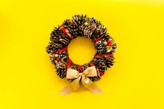 Christmas wreath made of pine cones on yellow background top view copy space. Christmas wreath made of pine cones on yellow background top view stock photo