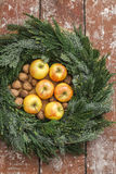 Christmas wreath made from pine twigs apples walnuts in the middle on wooden table Royalty Free Stock Photos