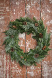 Christmas wreath made from pine twigs ornamented with pine cones on wooden table Royalty Free Stock Photos